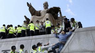 Policemen detain university students on a statue of King Sejong the Great during a protest against South Korean President Park Geun-hye, in Seoul - 8 May 2014