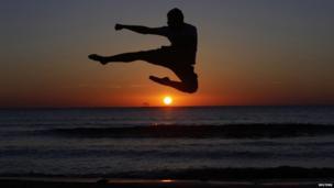 A man jumping into the air at a beach at sunset in Tripoli, Libya - Tuesday 6 May 2014