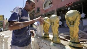 An Algerian plasterer paint sprays replicas of the World Cup trophy in Algiers, Tuesday 6 May 2014