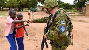 A European Union soldier bumping fists with boys in Bangui, CAR - Thursday 8 May 2014