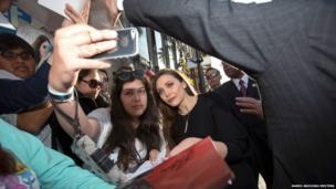Cast member Elizabeth Olsen (right centre) poses with a fan
