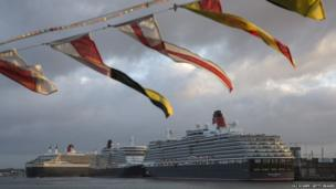 The Queen Mary 2 (left) ocean liner sails into dock alongside her sisters ships Queen Elizabeth (centre) and Queen Victoria