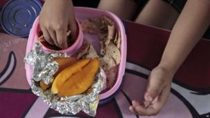 Baani, a 5-year-old Indian schoolgirl, eats her lunch prepared by her mother, consisting of flatbread, a turnip dish and mangoes, at a school in Jammu, India.
