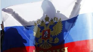"A woman holds a Russian national flag during a rally to support the self-rule ""referendums"" for the Ukrainian provinces of Donetsk and Lugansk in central Simferopol on May 11, 2014"