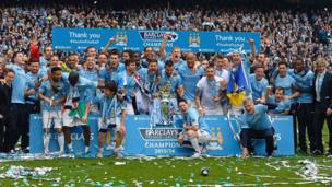 Manchester City players celebrate with trophy
