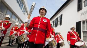 A military band perform with the Queen's Baton.