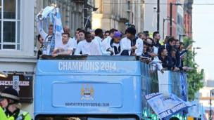 Manchester City team on top of bus holding trophy