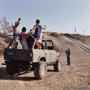 A man takes pictures of people in a Jeep