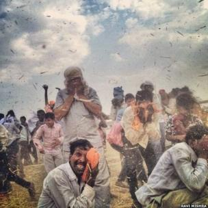 Supporters are engulfed in a momentary dust storm induced by BJP candidate Narendra Modi's helicopter, as he departs from a public meeting in Robertsganj, Varanasi.