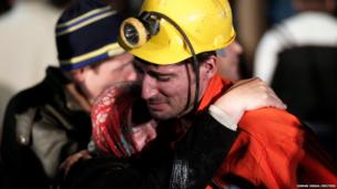 A miner hugs a relative in front of a coal mine site in Soma