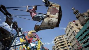 An Egyptian boy plays on a swing in downtown Cairo, Egypt, on 9 May 2014