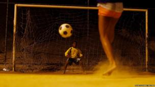 A boy kicks a penalty during a football training session at Sao Carlos favela in Rio de Janeiro