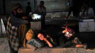 An Afghan man rests with his son at the roadside in Jalalabad