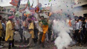 BJP supporters dance as they set off crackers as poll results come in at the party's headquarters in Ahmedabad, India
