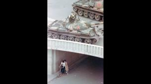 A Chinese couple on a bicycle take cover as tanks move overhead in Beijing on 5 June 1989