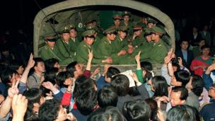 """Pro-democracy demonstrators raise their fists and flash """"victory"""" signs as they stop a military truck filled with soldiers on its way to Tiananmen Square"""
