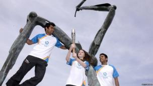 (L-R) Mukunda Measuria (25), Tara Donnelly (15) and Harshul Measuria (23) with the Commonwealth Games Baton at the Legs of Man Sculpture as it makes its way around the Isle of Man