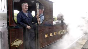 Driver Tommy Brown (left) and fireman Paul Rothwell hold the Commonwealth Games Baton aboard steam locomotive the Caledonia, which is on a narrow gauge railway in Douglas, as it makes its way around the Isle of Man