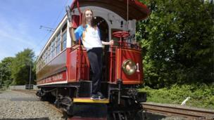 Gymnast athlete Grace Harrison holds the Commonwealth Games Baton aboard a tram at Laxey Station