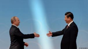 Russian President Vladimir Putin (left) is greeted by Chinese President Xi Jinping
