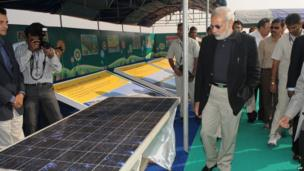 Narendra Modi (C) looks at solar panels before inaugurating the Gujarat Solar Park at Charanka village in Patan district, some 250kms from Ahmedabad, on December 30, 2010.
