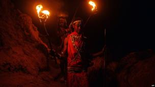 Young men dressed in Maasai costume holding flaming torches in a cave at Suswa, Kenya - Thursday 22 May 2014