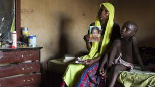 A woman holds up a photo of her abducted daughter as she sit on a bed next to her son, Maiduguri, Nigeria - Wednesday 21 May 2014