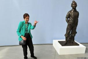 Fanny Rodwell, the widow of Tintin creator Herge, poses next to a sculpture of the comic book character