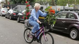 A woman on a bicycle carrying plants purchased during the final day sale at the RHS Chelsea Flower Show