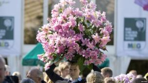 A man leaves carrying flowers after stock was sold off on the final day of the Chelsea Flower Show