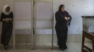 Egyptian women prepare to cast their votes at a polling station on the second day of Egypt's presidential election in the capital Cairo