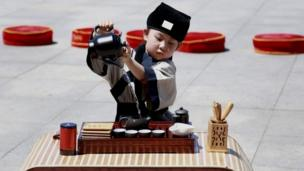 A Chinese child wearing costumes performs a tea ceremony ahead of the Dragon Boat Festival in Shenyang, Liaoning province