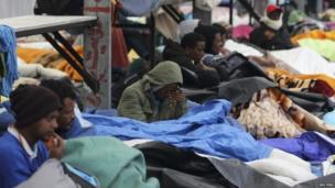 Eritrean migrants rest under blankets in the courtyard at a food distribution centre after they fled their makeshift camp to find shelter in Calais