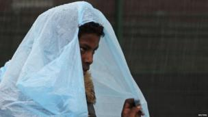 An African migrant shelters from heavy rain under a a bag during the daily food distribution at the harbour in Calais