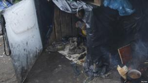 A migrant protects himself from the rain in the middle of makeshift shelters at the harbour in Calais