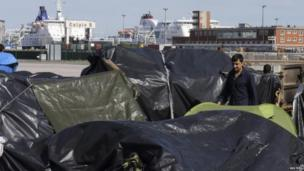 A migrant through a camp of makeshift shelters at the harbour in Calais