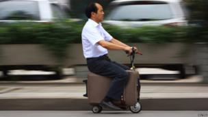 He Liang rides his home-made suitcase vehicle along a street in Changsha in China