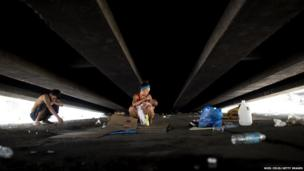 A homeless family takes shelter under a flyover in Manila on 29 May 2014