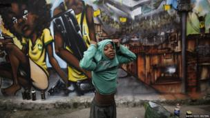 A young resident of Sao Paulo's Vila Flavia slum is surrounded by street art criticising the 2014 World Cup in Brazil on 28 May 2014.