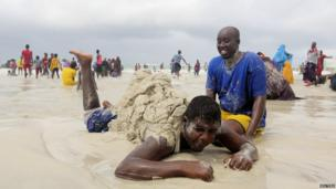 Residents play with sand at Lido beach, north of Somalia's capital Mogadishu on 23 May 2014
