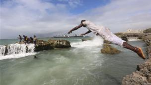 A man dives into the Indian Ocean waters at Lido beach, north of Somalia's capital Mogadishu on 23 May 2014