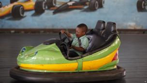 A child rides a bumper car in Abuja, Nigeria, on 27 May 2014
