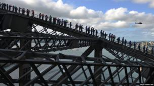 A world record is broken as 340 members of the Rotary Club climb Sydney Harbour Bridge simultaneously
