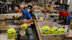 Indian workers at a manufacturing unit in Jalandhar stitch World Cup footballs