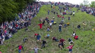 Competitors tumble down Coopers Hill in pursuit of a round Double Gloucester cheese