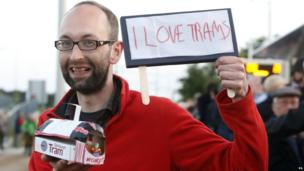 "Tram enthusiast with sign ""I love trams"""