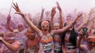 Participants dance at the end of the Colour Run around Wembley Stadium in London