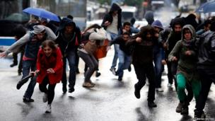 People run away from teargas fired during clashes between riot police and demonstrators during a protest in central Ankara