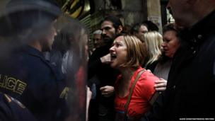 A woman shouts at a police officer during scuffles at the entrance the Finance Ministry in Athens as cleaning staff protest against the layoffs