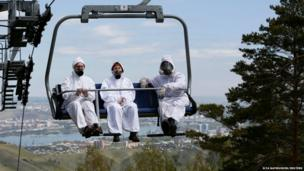 Employees of the Derate pest control company ride on a chair lift at the Bobrovy Log resort